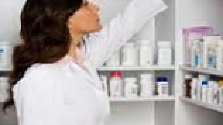 Farmacéutica cogiendo un envase de una estantería