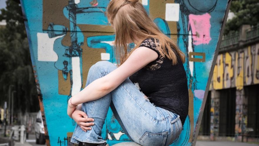 Chica sentada en un murete