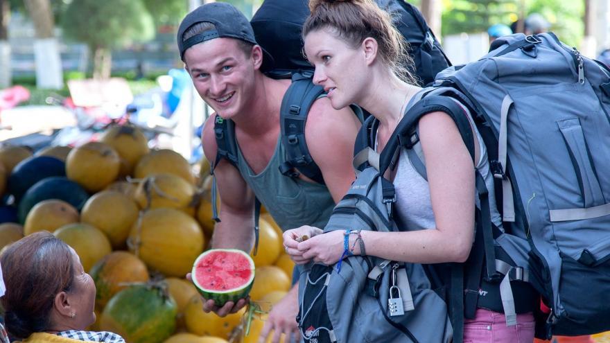 Dos mochileros comprando una sandia en un puesto callejero
