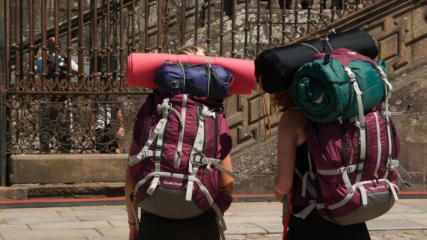 Dos mochileros de espaldas