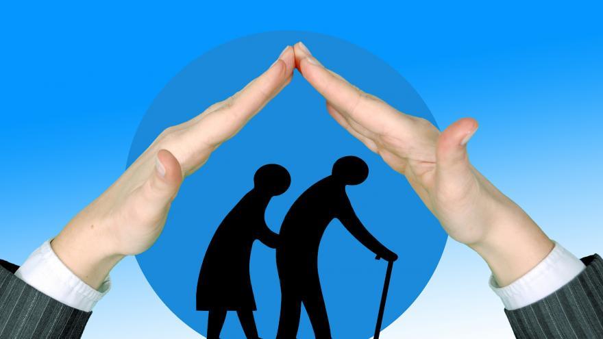 Manos protegiendo a una pareja de ancianos, como simbolo de inclusión social