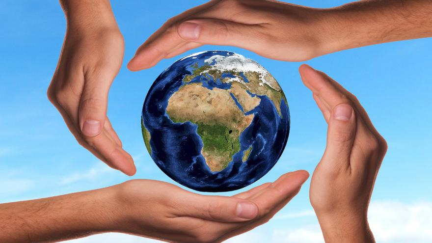 Manos rodeando un globo terráqueo, como símbolo de protección medioambiental