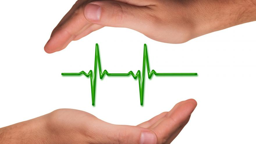 Manos protegiendo un gráfico de constantes vitales, como símbolo de salud