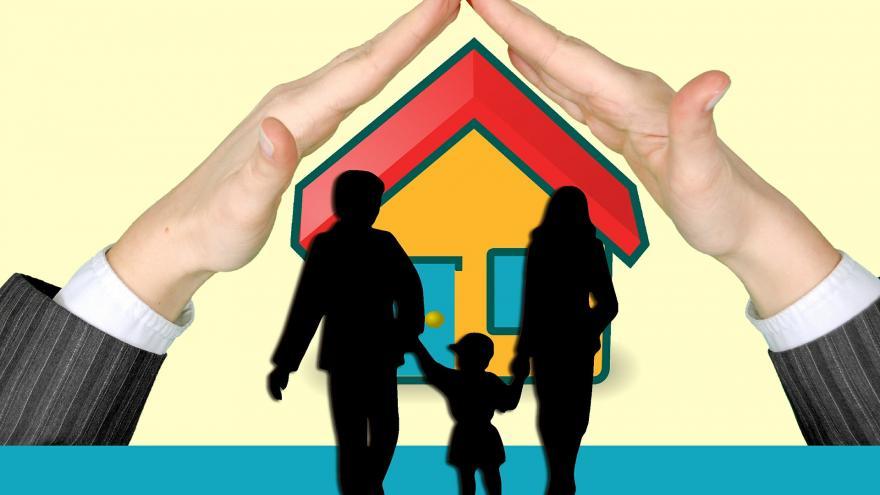 Manos protegiendo una casa y la silueta de una familia, como símbolo de vivienda asequible