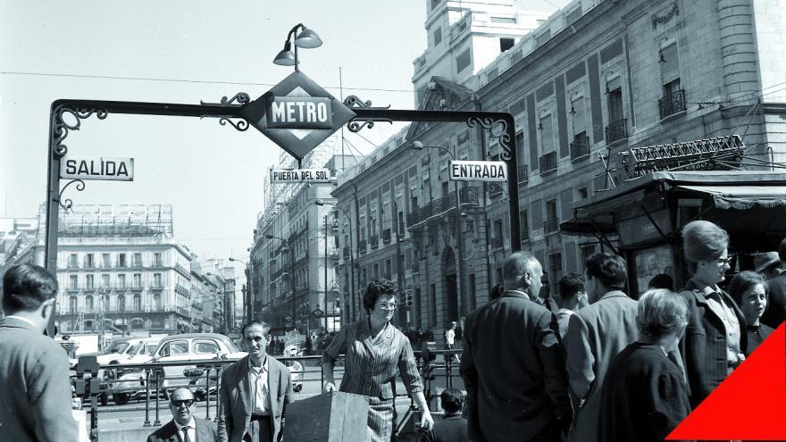 Imagen en blanco y negro de la parada de metro de SOL en la que se ven a un grupo de personas entrando y saliendo