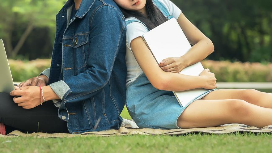 Estudiantes en un parque con sus ordenadores portátiles