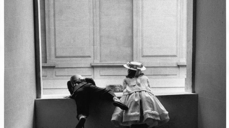 Dos niños asomados a una ventana