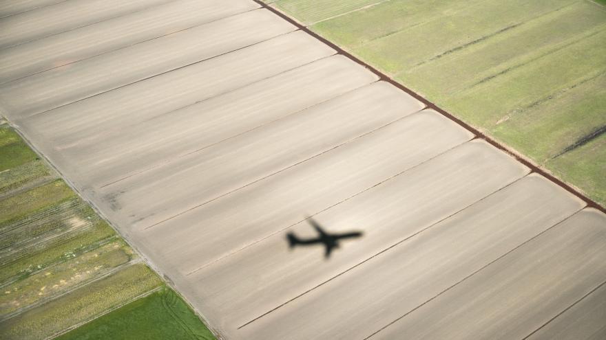 Sombra de un avión sobrevolando un campo