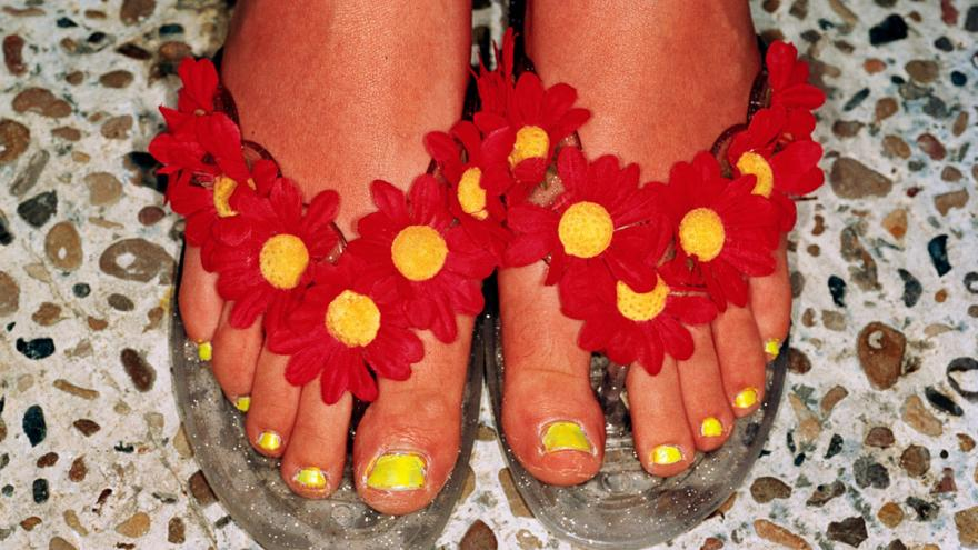 Pies femeninos con chanclas decoradas con flores