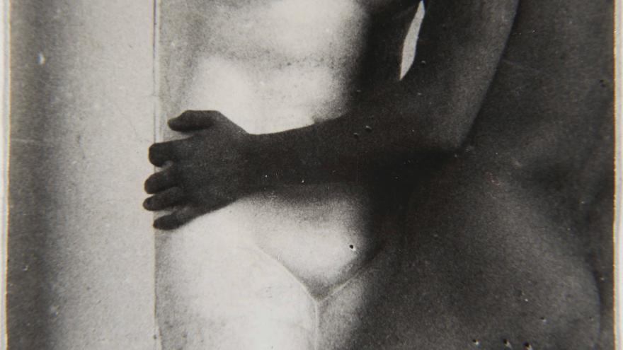 Cuero desnudo y bronceado coge de la cintura una escultura femenina clásica en mármol blanco