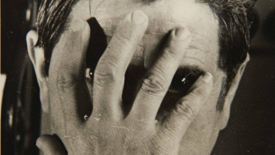 Fotografía en blanco y negro de un hombre ocultándo su rostro con una mano