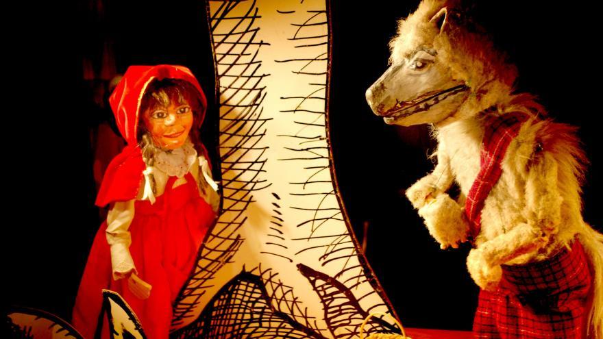 imagen en la que se ve al personaje de Caperucita detrás de un árbol con el lobo al lado