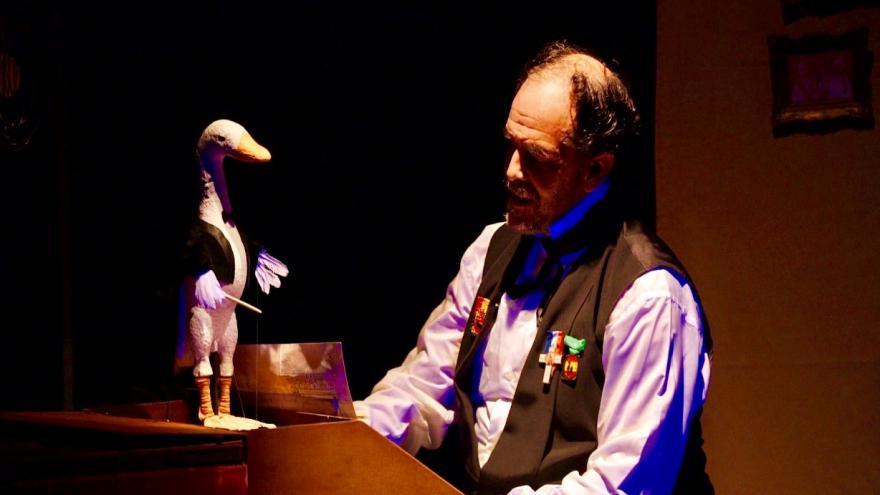 imagen en la que se ve al interprete en un piano con un títere de una oca