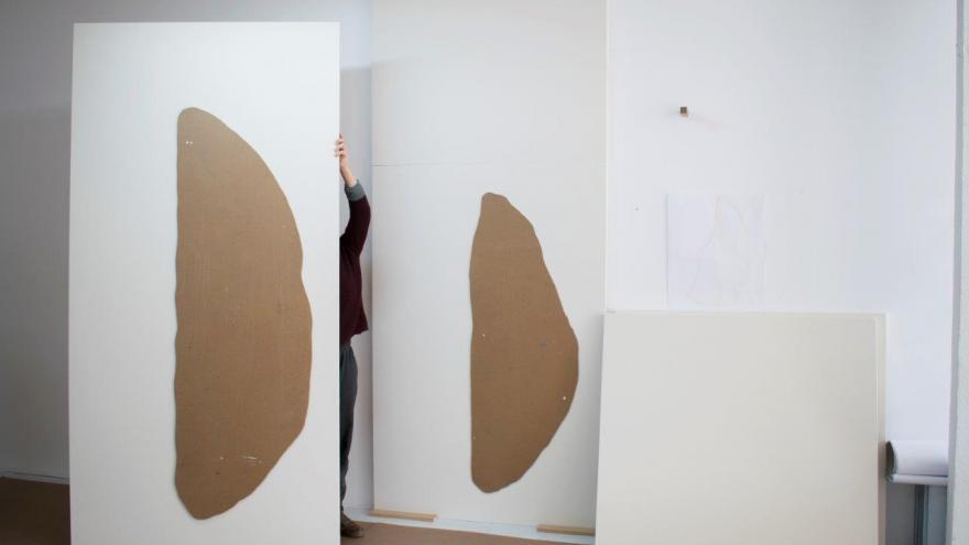 Tres paneles blancos con dibujos marrones en el centro