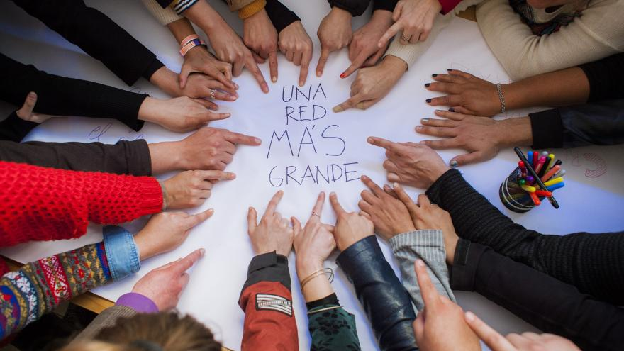 """Grupo de gente en círculo señalando con sus dedos en el centro un mensaje que pone """"Una red más grande"""""""