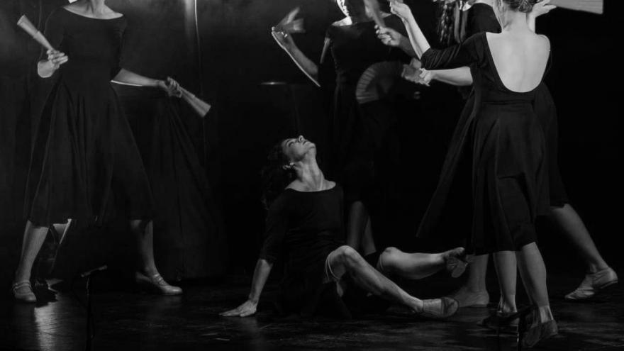 imagen en la que se ve a las bailarinas en el escenario vestidas de negro y con un abanico rojo rodeando a otra bailarina que está en el suelo