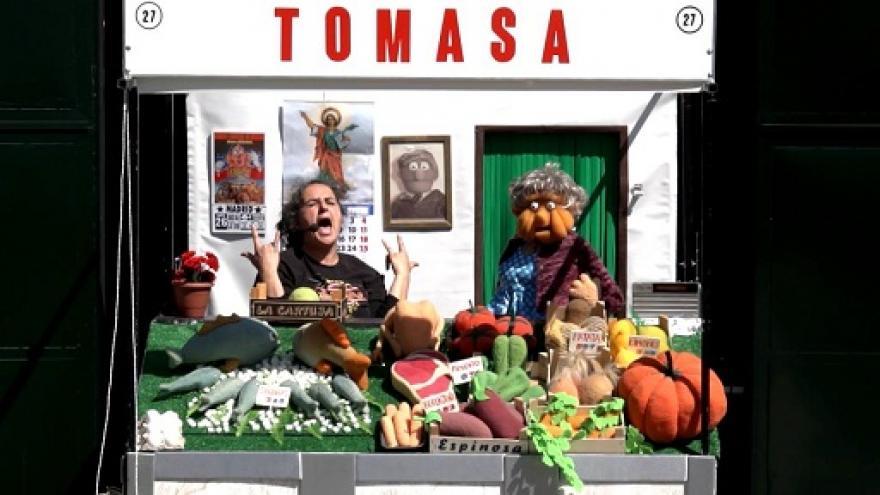 imagen en la que se ve al interprete atendiendo en un puesto de verduras junto con una marioneta