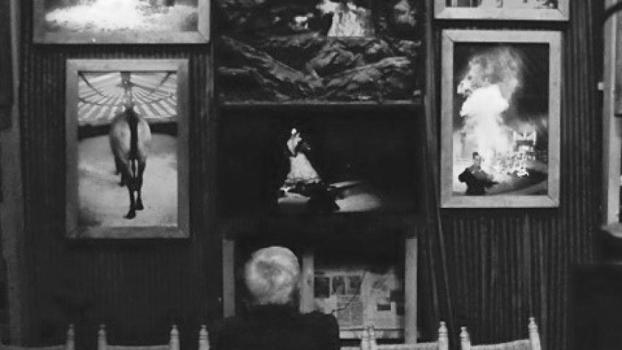imagen en la que se ve a una persona de espaldas sentada observando unos cuadros con tradiciones flamencas