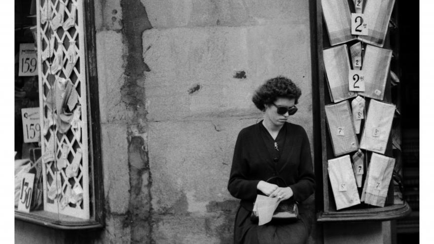 Foto en blanco y negro de una mujer sentada vendiendo cupones en la esquina de una calle de Barcelona