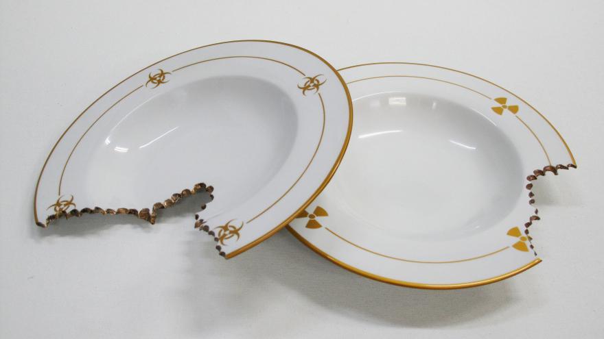 Dos platos blancos, uno de ellos roto y descascarillado