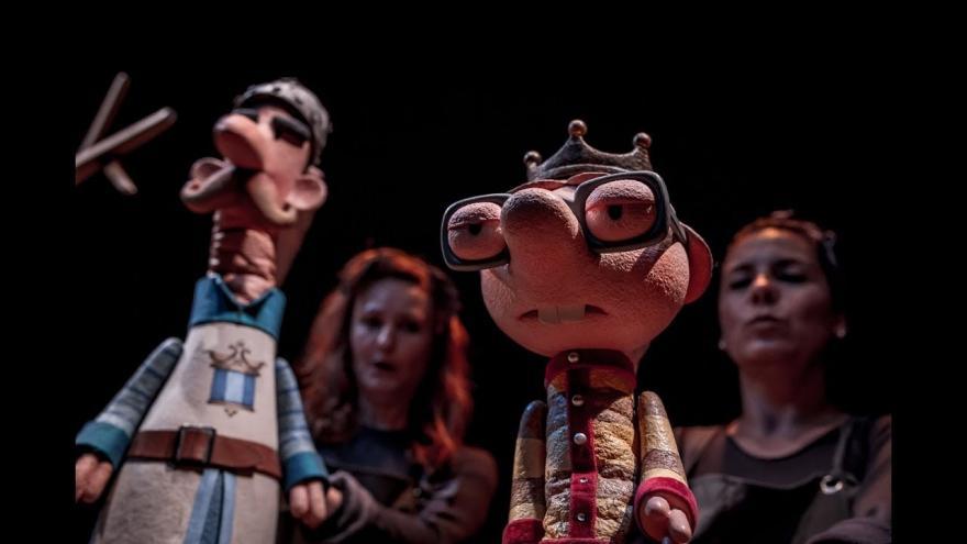 imagen en la que se ve a la interprete con varios títeres en el escenario