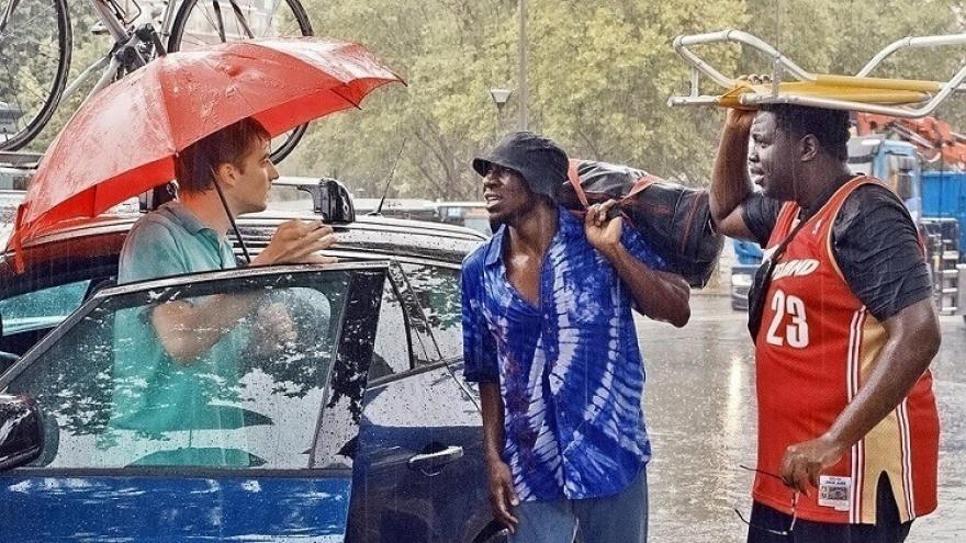 imagen de los actores con paraguas hablando frente a un coche