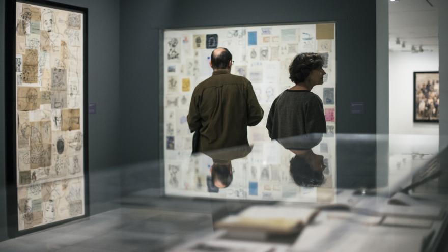 Dos visitantes observando dibujos realizados por Carmen Calvo