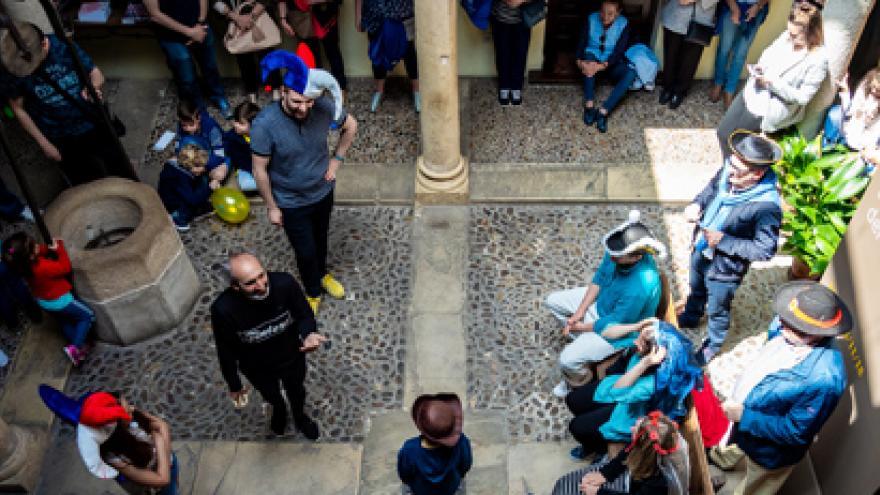 Grupo de espectadores en el patio del museo Cervantes antendiendo un espectáculo teatral