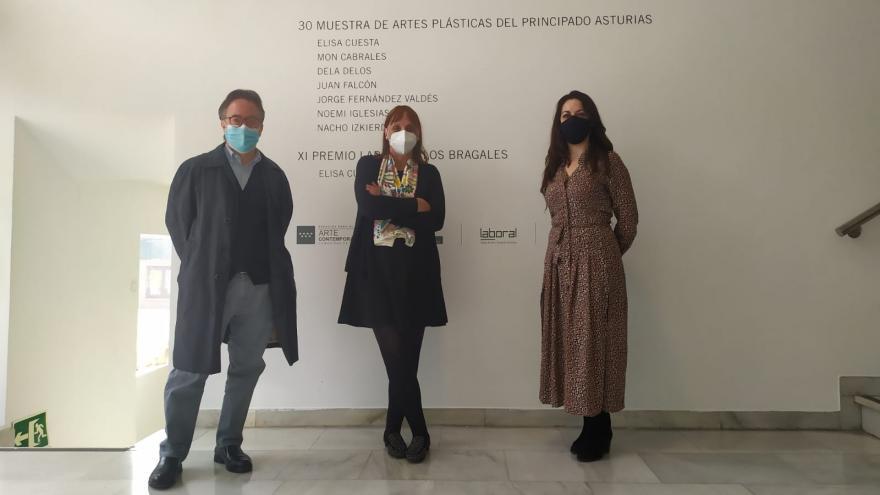 """Tres personas frente a una pared con el titulo de la exposición """"Muestra asturiana"""""""