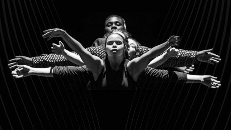 imagen en la que se ve a tres bailarines en escena en un movimiento de brazos