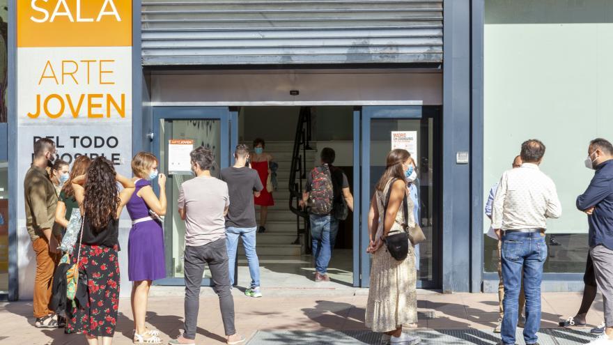 Grupo de personas en la puerta de una sala de exposiciones