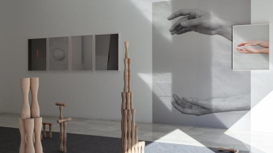 Fotografías de manos colgadas en una pared y juego infantil en madera sobre el suelo