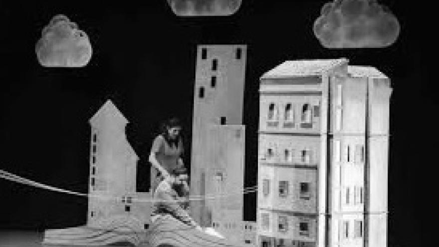 imagen del espectáculo Debajo del Tejado donde se ve a una actriz ante la escenografía con edificios detras