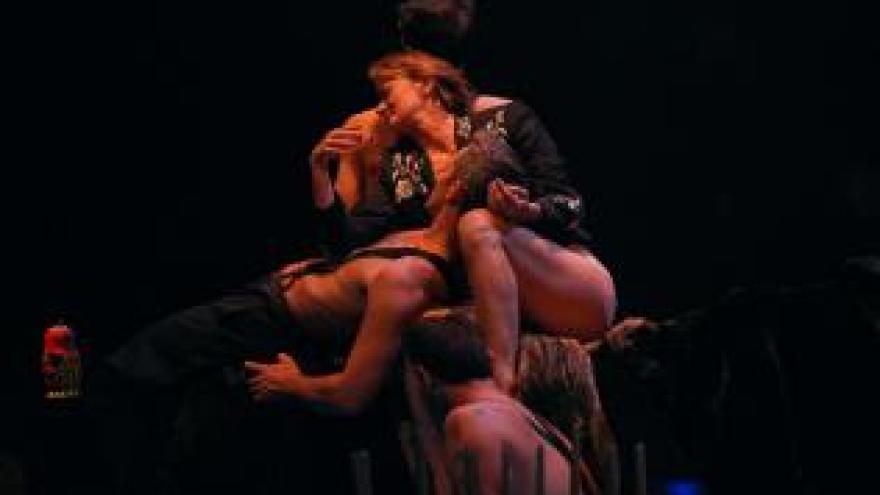 imagen en la que se ve en escena a varios bailarines enredando sus cuerpos
