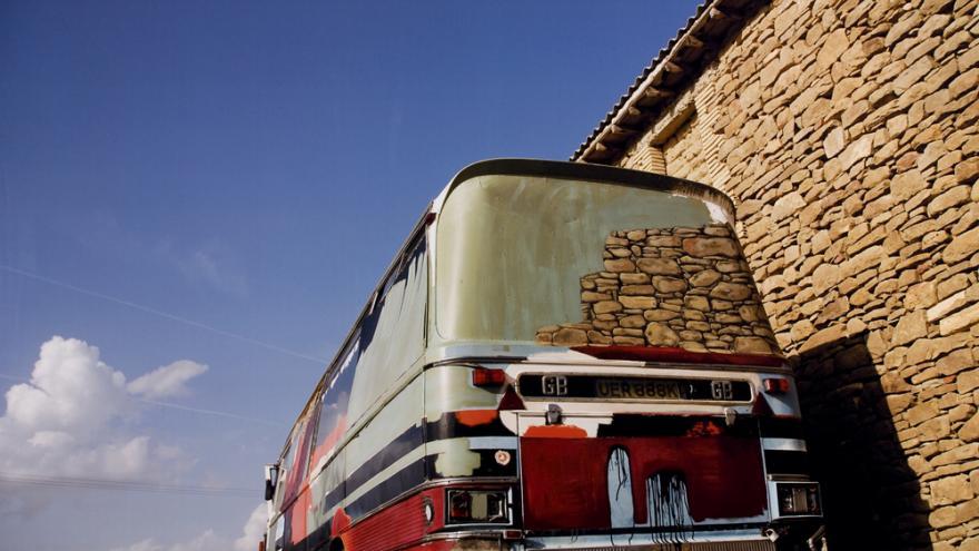 Autobús rojo apoyado en una tapia de piedra