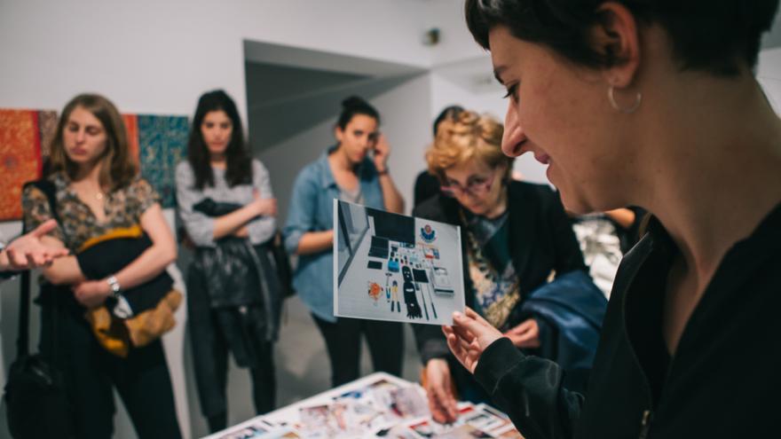 Grupo de gente joven mirando álbumes y fotos que la sala de Arte Joven y charlando entre ellos