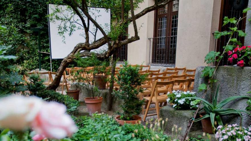 Jardín con sillas plegables y una pantalla de cine