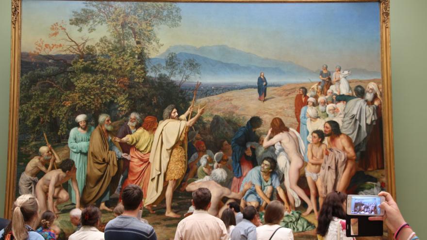 Grupo de personas observando un gran cuadro histórico con escena bíblica