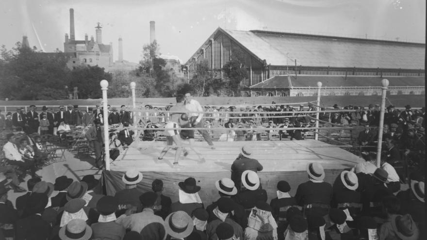 Foto en blanco y negro con un ring de boxeo y público observando el espectáculo
