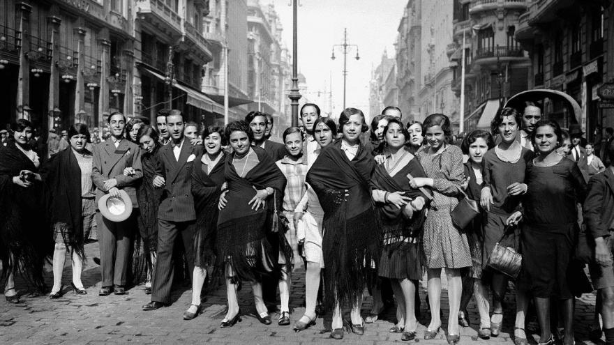 Grupo de personas en la calle mirando y sonriendo a la cámara