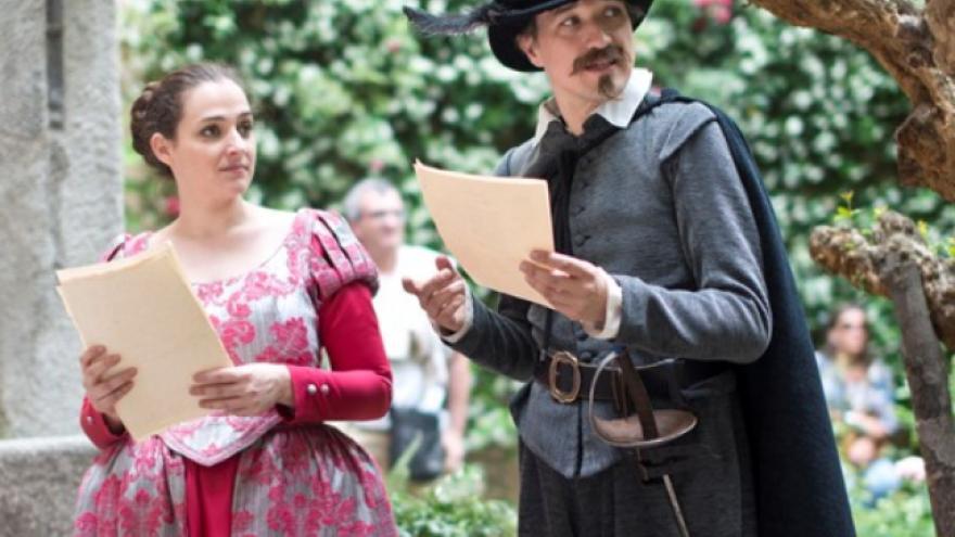 Actor y actriz en un jardín y vestidos de época