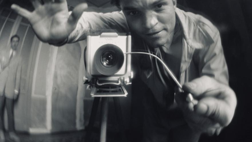 Autorretrato de Francesc Catalá Roca frente a un espejo que distorsiona su imagen y la de la cámara con el trípode