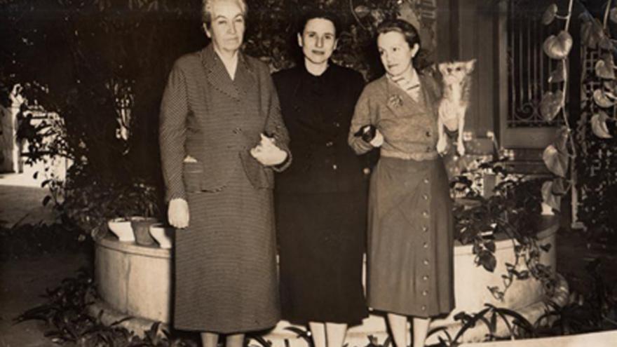 3 mujeres posando, una de ella con un perrito en brazos