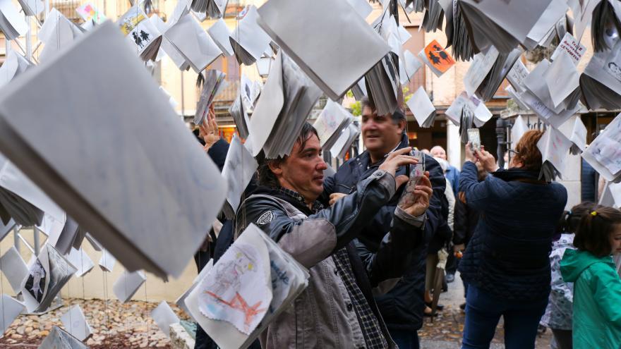 Gente hojeando libros que están suspendidos en el aire