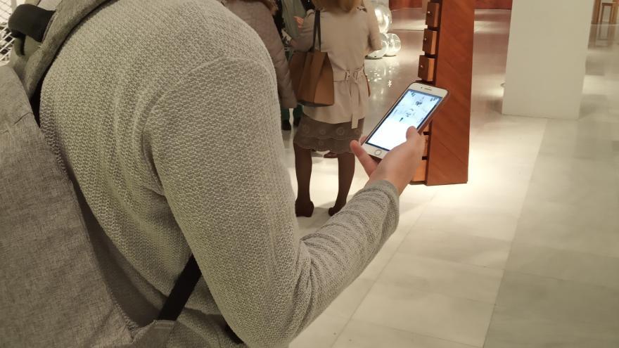Hombre mirando la pantalla de un móvil mientra visita una exposición