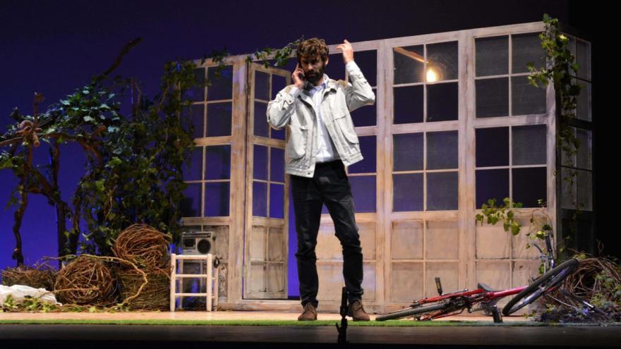 imagen en la que se ve a un actor en el escenario con la mascarilla y hablando por teléfono
