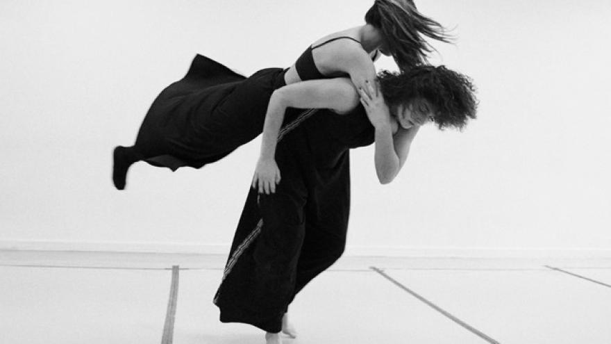 imagen en la que se ve a dos bailarinas una cargando a otra en la espalda