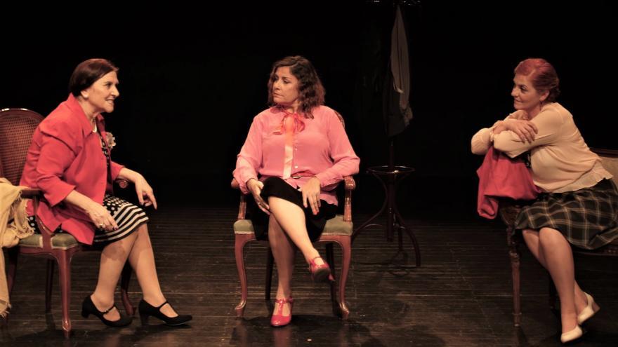 imagen en la que se ve a tres mujeres sentadas en una silla en el escenario hablando