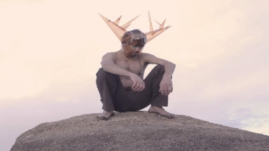 imagen de un hombre sobre una piedra con una especie de cuernos de ciervo