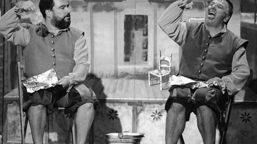 imagen en la que se ve a dos integrantes de la compañía actuando sentados